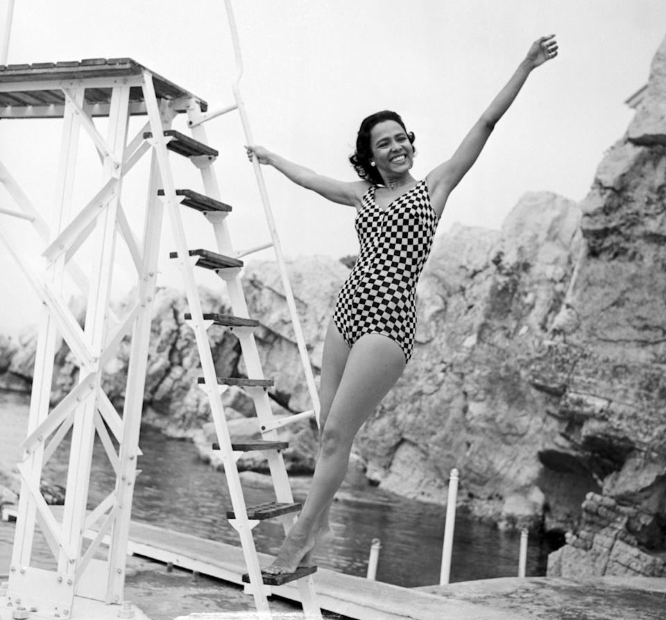 <p>After the success of <em>Carmen Jones</em><em>,</em> Dandridge traveled to the South of France for the annual Cannes Film Festival. Here, the actress poses in a geometric one-piece as the press catches her taking a dip in the Mediterranean Sea. </p>