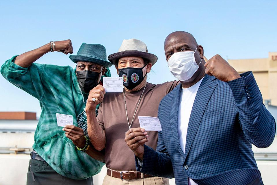 <p>Arsenio Hall, Danny Trejo and Magic Johnson proudly pose with their COVID-19 vaccine cards after getting their shots, as part of a vaccination awareness event at USC, on Wednesday in L.A.</p>