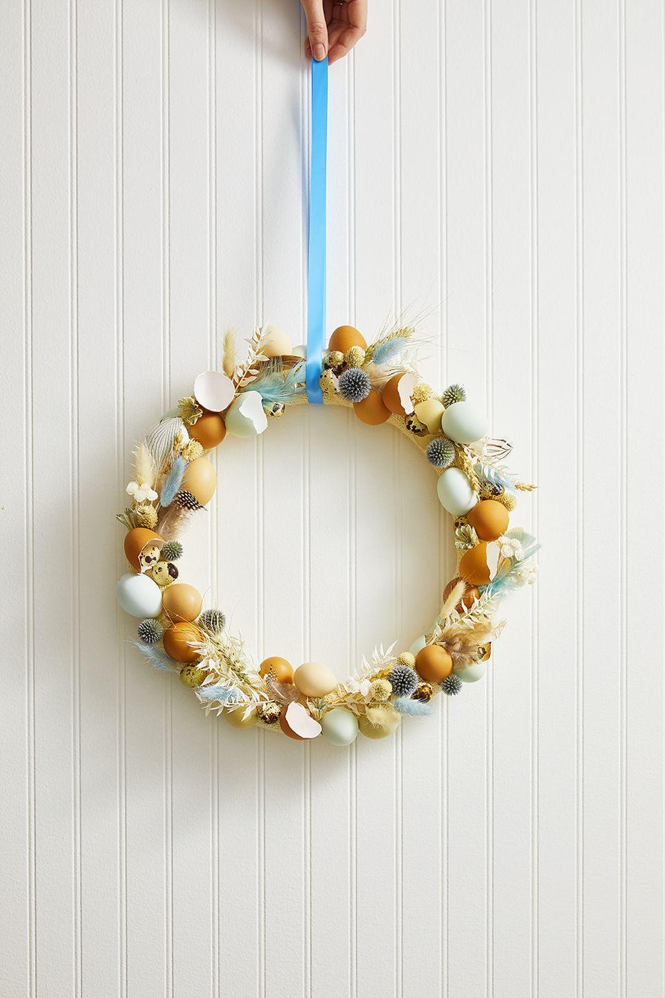 <p>To welcome guests in the sweetest way, wrap a foam wreath form with burlap. Use a hot glue to attach blown out eggs, broken egg shells, quail eggs, feathers, dried leaves and flowers to the wreath, overlapping until the entire form is covered.</p>