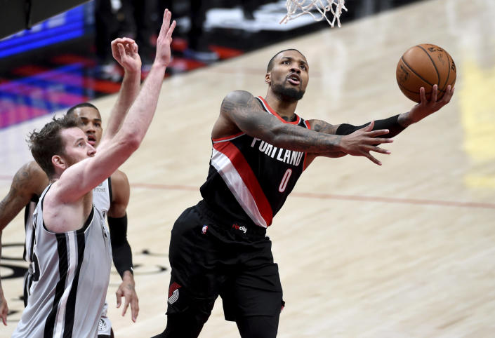 Portland Trail Blazers guard Damian Lillard, right, drives to the basket against San Antonio Spurs center Jakob Poeltl, left, during the second half of an NBA basketball game in Portland, Ore., Monday, Jan. 18, 2021. (AP Photo/Steve Dykes)