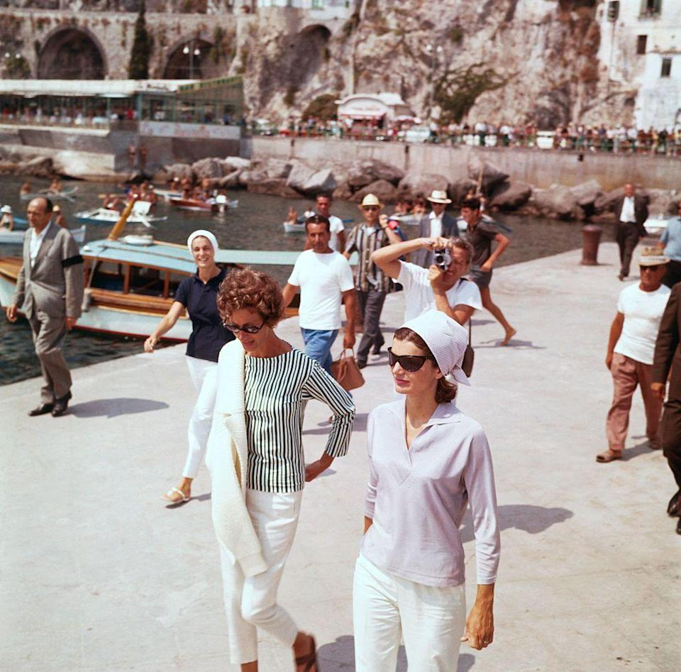 <p>Wearing a kerchief, collared sweater, and white pants, Jackie Kennedy strolls in Amalfi during a holiday on the Mediterranean coast with Marella Agnelli.<br></p>