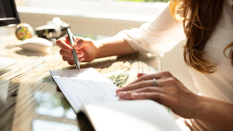 Businesswoman's Hand Signing Cheque On Wooden Desk.