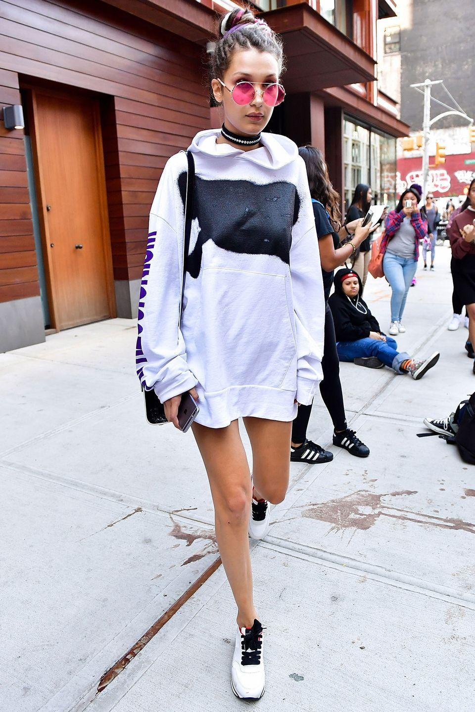 <p>In oversized hooded sweater, choker necklace, statement sunglasses and sneakers on the streets of Manhattan.</p>
