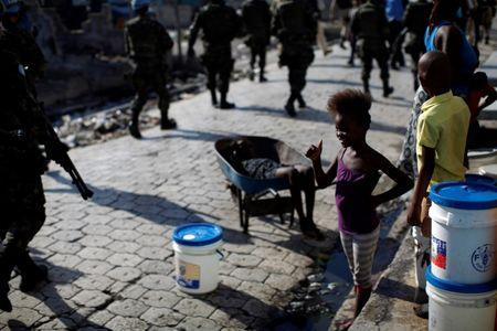 A girl greets U.N. peacekeepers, Haitian national police officers and members of UNPOL (United Nations Police) as they walk along a street during a patrol in Cite Soleil, Port-au-Prince, Haiti, March 3, 2017. Picture taken March 3, 2017. REUTERS/Andres Martinez Casares