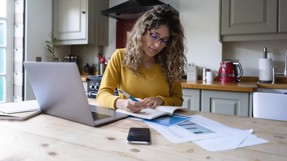 Beautiful young woman with curly hair working from home writing on notepad and using laptop and documents - Lifestyles.