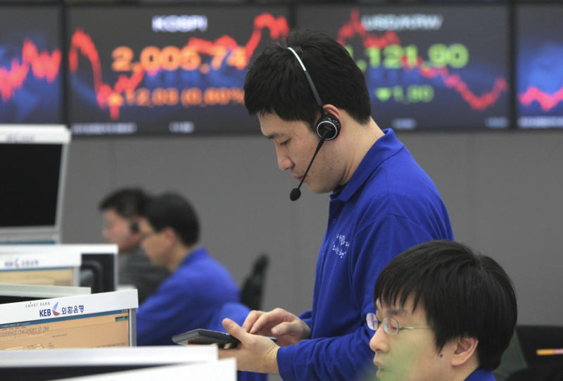 A currency trader uses a calculator in front of a screen showing the Korea Composite Stock Price Index, center left, and the exchange rate between the U.S. dollar and the South Korean won at the foreign exchange dealing room of the Korea Exchange Bank headquarters in Seoul, South Korea, Monday, Feb. 13, 2012.  South Korea's Kospi rose 0.60 percent, or 12.03 points, to close at 2,005.74. (AP Photo/Ahn Young-joon)