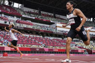 Nathan Crumpton, right, of American Samoa, competes in a heat of the men's 100-meter run at the 2020 Summer Olympics, Saturday, July 31, 2021, in Tokyo. (AP Photo/David J. Phillip)