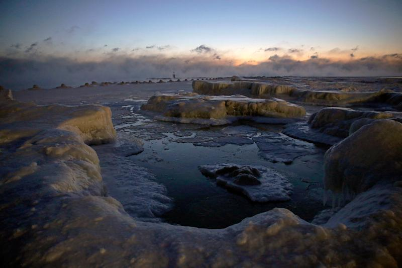 Ice forms along the shore of Lake Michigan before sunrise, Wednesday, Jan. 30, 2019, in Chicago. A deadly arctic deep freeze enveloped the Midwest with record-breaking temperatures on Wednesday, triggering widespread closures of schools and businesses, and prompting the U.S. Postal Service to take the rare step of suspending mail delivery to a wide swath of the region. (AP Photo/Kiichiro Sato)