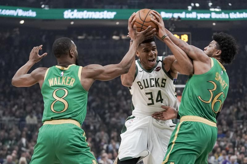 Milwaukee Bucks' Giannis Antetokounmpo tries to drive between Boston Celtics' Kemba Walker and Marcus Smart during the first half of an NBA basketball game Thursday, Jan. 16, 2020, in Milwaukee. (AP Photo/Morry Gash)