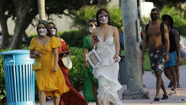 PHOTO: People wearing protective face masks walk along Ocean Drive during the coronavirus pandemic, July 24, 2020, in Miami Beach, Fla. (Lynne Sladky/AP)