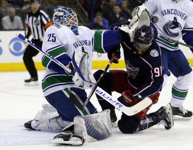 Vancouver Canucks goalie Jacob Markstrom, left, of Sweden, stops a shot in front of Columbus Blue Jackets forward Anthony Ducclair during the second period of an NHL hockey game in Columbus, Ohio, Tuesday, Dec. 11, 2018. (AP Photo/Paul Vernon)