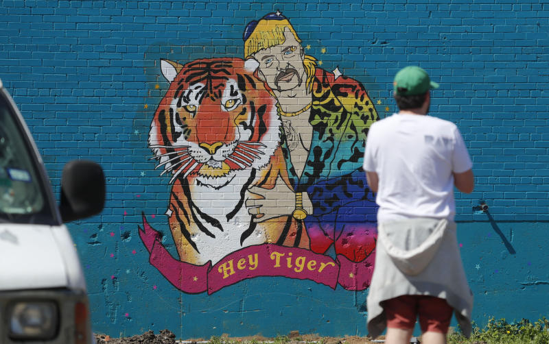 "A man looks at a mural depicting Joseph Maldonado-Passage, also known as ""Joe Exotic,"" in Dallas, Friday, April 10, 2020. The Netflix series ""Tiger King,"" has become popular watching during the COVID-19 outbreak. Maldonado-Passage was convicted in an unsuccessful murder-for-hire plot. (AP Photo/LM Otero)"