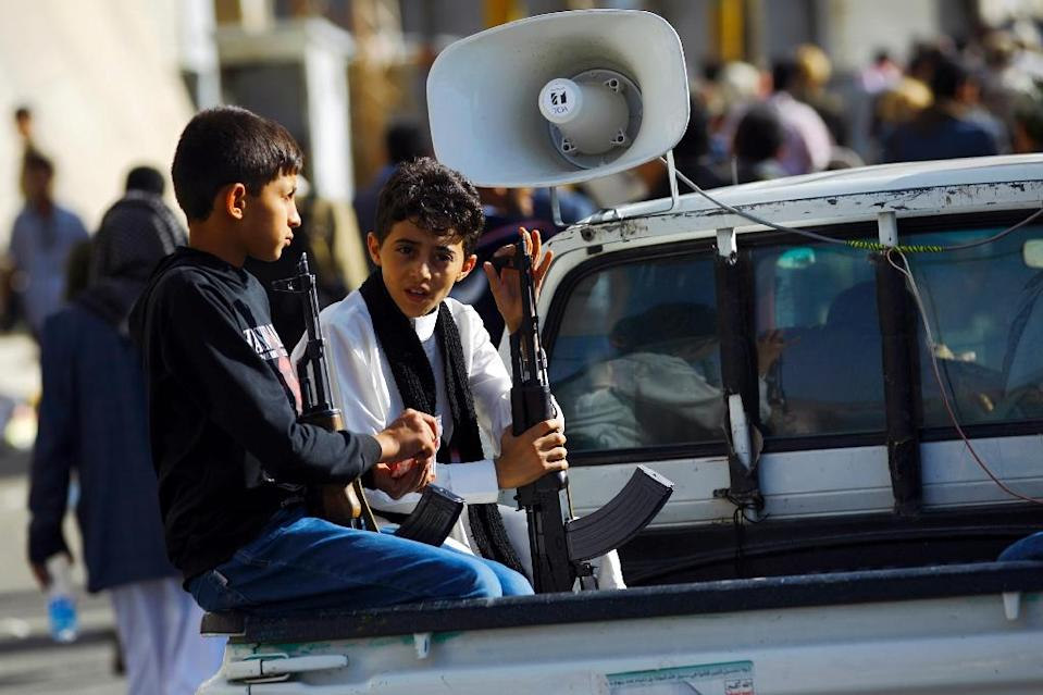 Yemeni boys hold weapons as they sit on a pick-up truck during a demonstration by supporters of the Shiite Huthi movement in Sanaa on April 22, 2015 (AFP Photo/Mohammed Huwais)