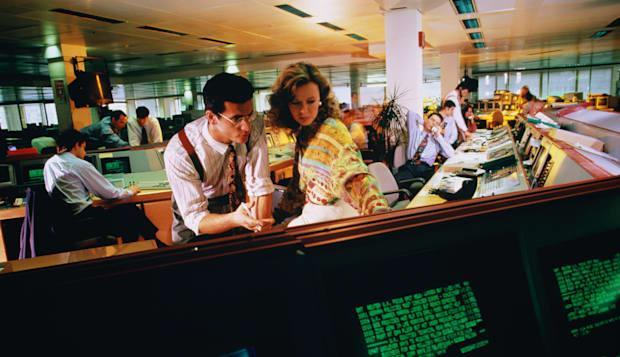 Traders working out figures in dealing room