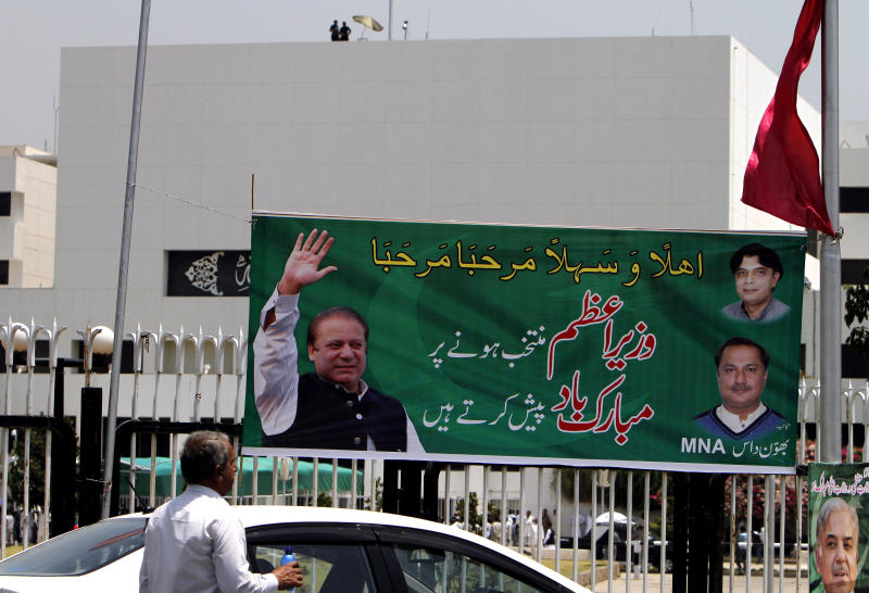 A banner with the photo of Pakistan's upcoming Prime Minister Nawaz Sharif, is displayed near the National Assembly building, background, in Islamabad, Pakistan, Wednesday, June 5, 2013. Pakistan's parliament is set to elect Sharif as prime minister on Wednesday, completing a historic transition of power in the country's coup-riddled history. (AP Photo/Anjum Naveed)