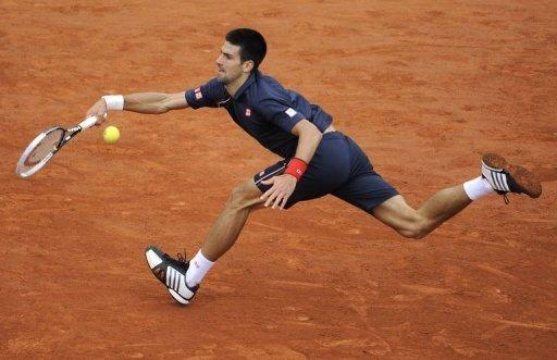 Serbia's Novak Djokovic stretches to make a return to Rafael Nadal during the French Open men's singles final at Roland Garros stadium in Paris on June 10. Nadal took the first two sets 6-4, 6-3 before Djokovic fought back to win the third 6-2 on a rain-affedted day