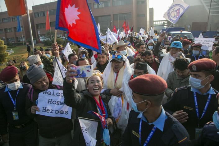 A Nepalese woman takes selfie with the all-Nepalese mountaineering team that became the first to scale Mount K2 in winter as they arrive at Tribhuwan International airport in Kathmandu, Nepal, Tuesday, Jan. 26, 2021. (AP Photo/Niranjan Shrestha)
