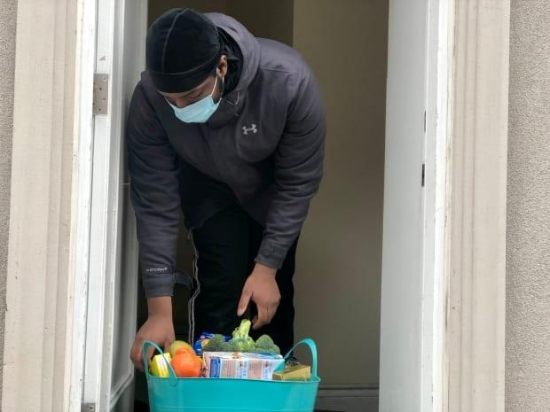 Shomari Mabayeke looks through a basket of groceries delivered to him by StepsStones for Youth, a charity that helps young people transition out of the child-welfare system.