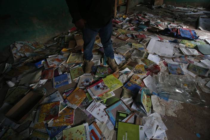 A man stands on textbooks strewn about the floor of a school that has an exterior still pocked with bullet holes in the ghost village of Paraiso de Tepila, Guerrero state, Mexico, Friday, April 30, 2021. More than two years ago all 35 families that lived in Paraiso de Tepila fled after it was overrun by criminals. (AP Photo/Marco Ugarte)