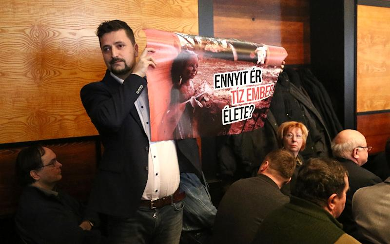 """Hungarian Jobbik party MP Lajos Kepli holds a sign reading:"""" That the value of ten people"""", in Veszprem court on January 28, 2016 (AFP Photo/Ferenc Isza)"""