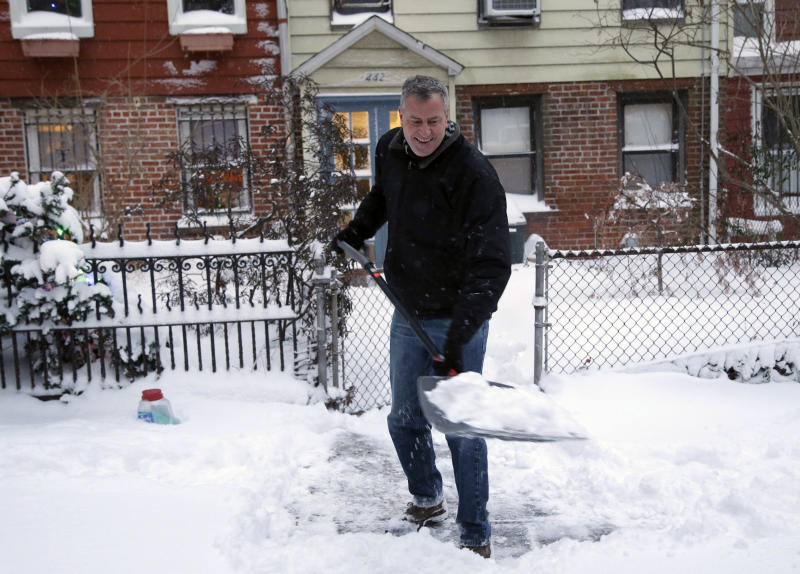 FILE - In this Jan. 3, 2014, file photo, New York City Mayor Bill de Blasio shovels the sidewalk in front of his house in New York. De Blasio's first 100 days as mayor of New York were marked in nearly equal measures by accomplishing campaign goals and committing political blunders. The mayor's managerial skills were called into question after he was forced to admit that the city did not plow several neighborhoods effectively during one of the winter's many snowstorms. (AP Photo/Seth Wenig, File)