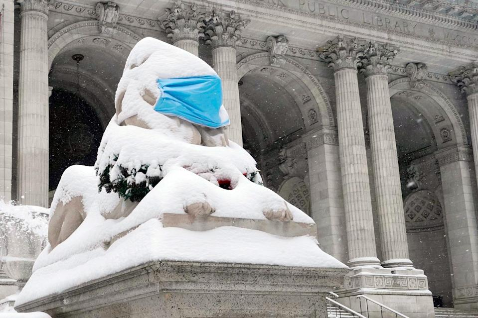 <p>One of the two masked lion statues outside the New York Public Library is hardly visible below the snow.</p>