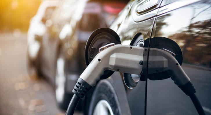 A photo of an electric car with the charger plugged in.
