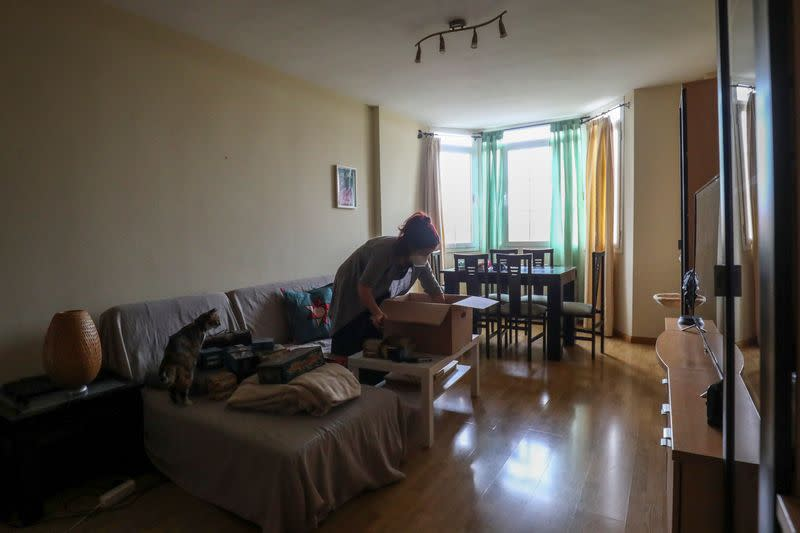 Ines Alcolea unpacks moving boxes in her new rented apartment in Fuensalida