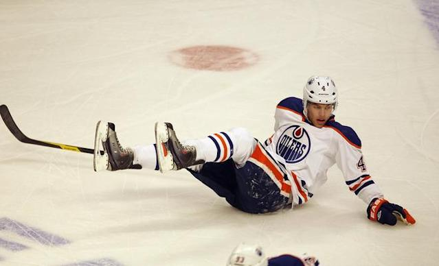 CHICAGO, IL - JANUARY 02: Taylor Hall #4 of the Edmonton Oilers slides across the ice after falling against the Chicago Blackhawks at the United Center on January 2, 2012 in Chicago, Illinois. (Photo by Jonathan Daniel/Getty Images)