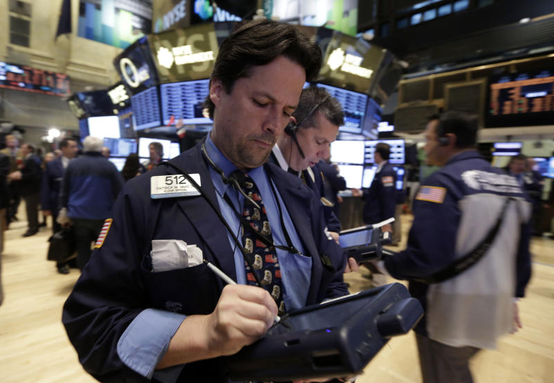 FILE - In this Nov. 22, 2013 file photo, trader Patrick McKeon, left, works on the floor of the New York Stock Exchange. World stock markets were mostly lower Tuesday, Nov. 26, 2013, after a lull in Wall Street's record-breaking run ahead of a U.S. holiday. (AP Photo/Richard Drew, File)