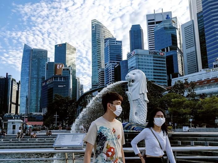"""A couple with face masks walk through Singapore during the coronavirus outbreak on March 14, 2020. <p class=""""copyright""""><a href=""""http://www.apimages.com/metadata/Index/Virus-Outbreak-Singapore/650f06888bd446329a60db67cc18235d/82/0"""" rel=""""nofollow noopener"""" target=""""_blank"""" data-ylk=""""slk:Ee Ming Toh/AP"""" class=""""link rapid-noclick-resp"""">Ee Ming Toh/AP</a></p>"""