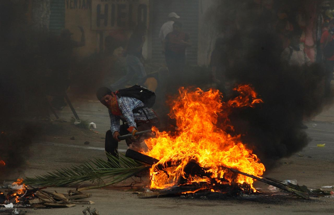 <p>A protester from the National Coordinator of Education Workers (CNTE) teachers union is seen next to a burning barricade after clashes with riot police during a protest against President Enrique Peña Nieto's education reform, near in the town of Nochixtlan, Mexico, June 19, 2016. (Reuters/Jorge Luis Plata) </p>