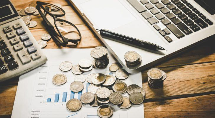 A laptop, pencil, pair of eyeglasses, and many coins rest on a wooden table.