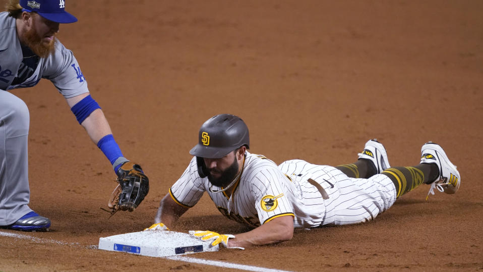 San Diego Padres' Eric Hosmer, right, slides into to third safely as Los Angeles Dodgers' Justin Turner, left, makes a late tag while advancing on a single by Tommy Pham during the second inning in Game 3 of a baseball National League Division Series Thursday, Oct. 8, 2020, in Arlington, Texas. (AP Photo/Tony Gutierrez)
