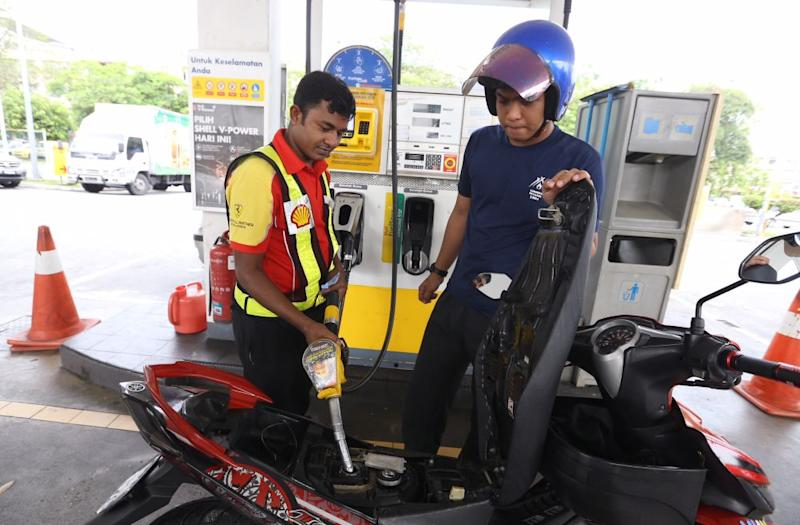 A pump attendant refuels a bike at the Bandar Puteri Puchong Shell petrol station on May 15, 2018. — Picture by Zuraneeza Zulkifli