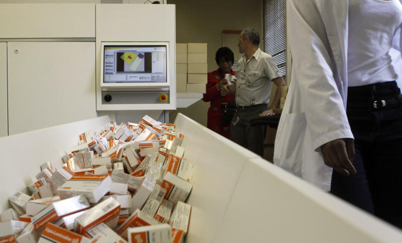 FILE - In this Nov. 15, 2012 file photo a newly mechanized pharmaceutical machine that helps pharmacists dispense medicine is loaded with ARV medication, at the U.S. sponsored Themba Lethu, HIV/AIDS Clinic, at the Helen Joseph hospital, in Johannesburg. To give people with HIV their best shot at survival and to stop the virus from spreading, patients should be treated much earlier than has previously been the case in developing countries, according to new guidelines issued Sunday June 30, 2013 at an AIDS meeting in Malaysia by the World Health Organization. (AP Photo/Denis Farrell, File)