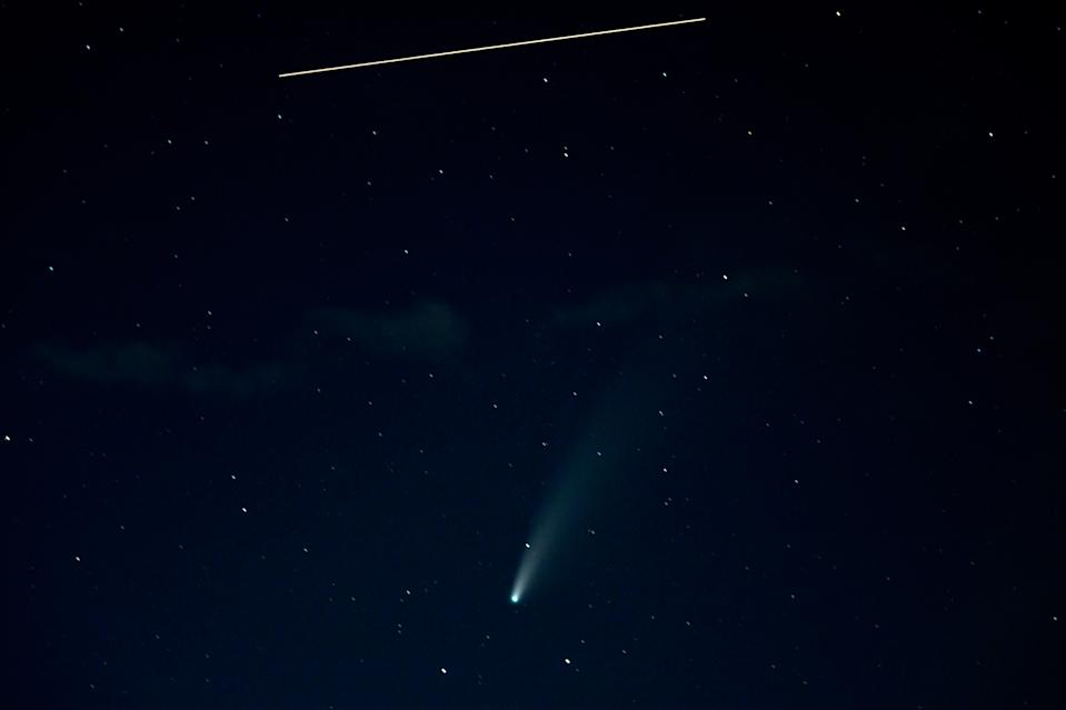 This striking photo showcases both comet NEOWISE and the International Space Station. This 10-second exposure image shows the space station's movement as a straight, yellow line and the comet as a diffuse, glowing object seemingly falling from the sky. Comet NEOWISE made its closest approach to Earth yesterday (July 23).