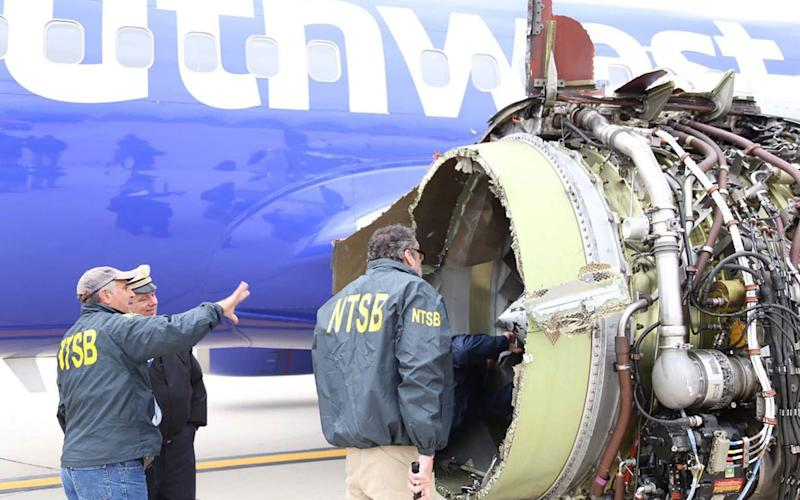 Investigators examine the damage to the engine of the Southwest Airlines plane - AFP