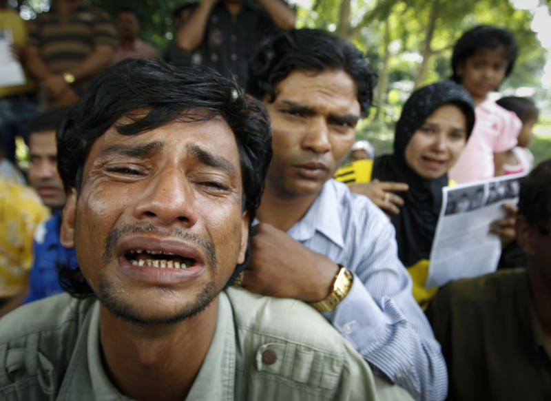 A Rohingya protester cries as he holds a placard during a rally to call for an end to the ongoing unrest and violence in Myanmar's Rakhine state, in Kuala Lumpur, Malaysia, Tuesday, June 12, 2012. (AP Photo/ Vincent Thian)