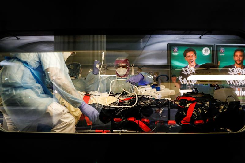 A patient is moved onto a TGV carriage to be transported out of Paris. (Thomas Samson/Pool via REUTERS)