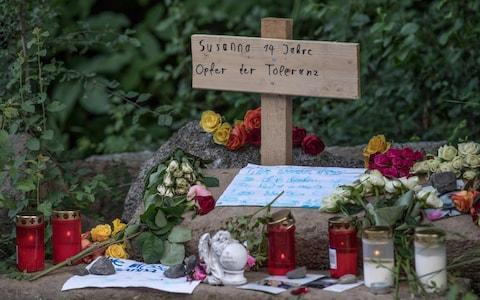 <span>A cross with a sign reading 'Susanna, 14 year-old, victim of tolerance' is placed among flowers and candles at a makeshift memorial </span> <span>Credit: BORIS ROESSLER/AFP/Getty Images </span>