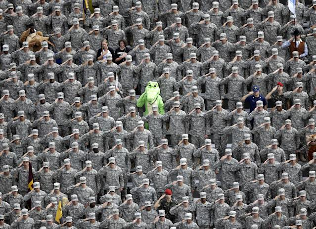 A cadet dressed in an alligator mascot outfit joins fellow cadets in a salute during the national anthem before an NCAA college football game between Army and Stanford on Saturday, Sept. 14, 2013, in West Point, N.Y. (AP Photo/Mike Groll)