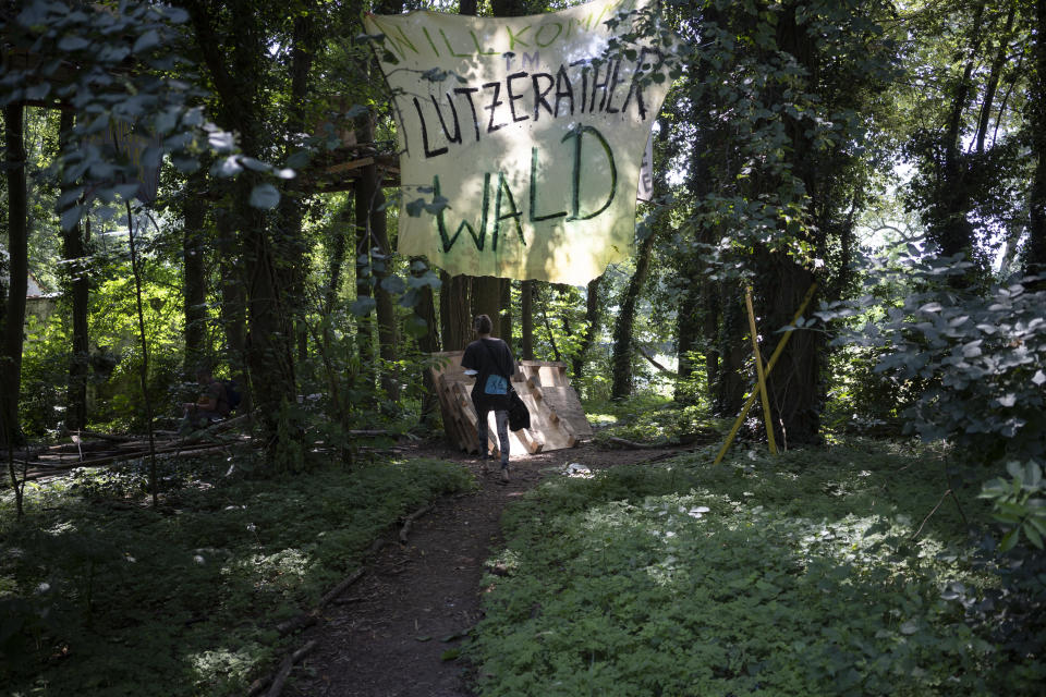 """A banner reading '""""Welcome in Luetzerath forest"""" hangs in a forest in Luetzerath, Germany, where activists camp to try and stop the construction of a coal mine, Tuesday, July 20, 2021. The village is located just a few hundred meters from a vast pit where German utility giant RWE is extracting lignite coal to burn in nearby power plants.(AP Photo/Bram Janssen)"""