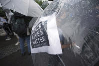 A protester, with a banner seen through her umbrella, take part in a solidarity rally for the death of George Floyd in Tokyo Sunday, June 14, 2020. Floyd died after being restrained by Minneapolis police officers on May 25. (AP Photo/Eugene Hoshiko)