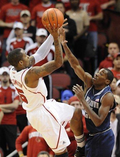 Louisville's Chris Smith, left, shoots over Georgetown's Jason Clark during the first half of an NCAA college basketball game Wednesday, Dec. 28, 2011, in Louisville, Ky. (AP Photo/Timothy D. Easley)