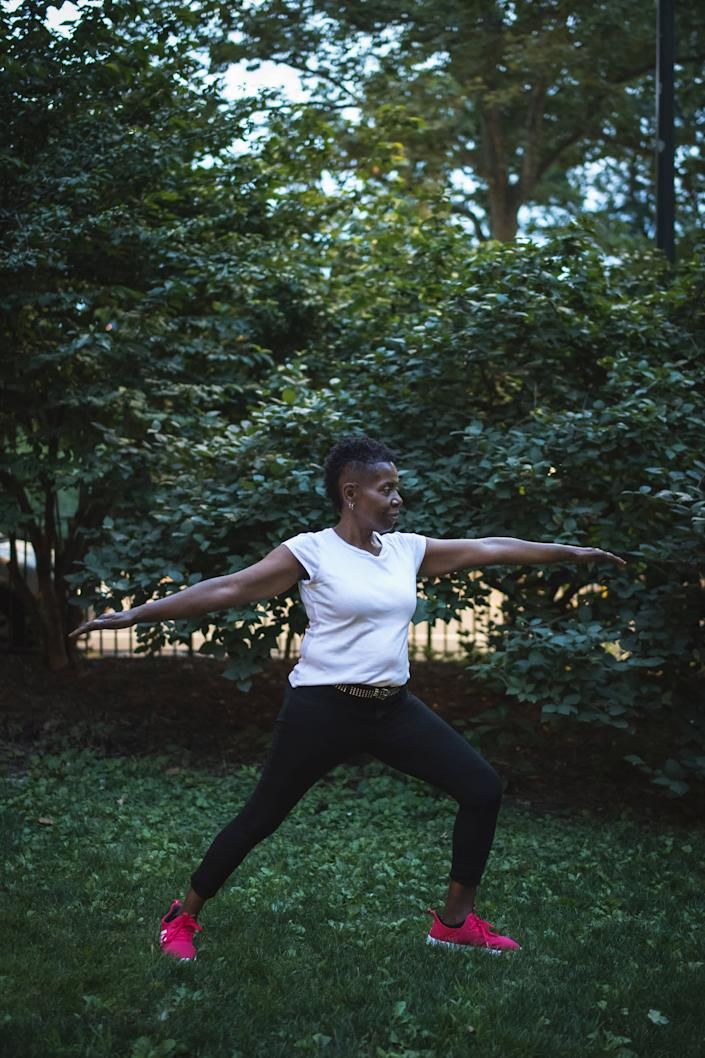 Woodson holds a yoga warrior pose in Central Park on July 16 | Kholood Eid for TIME