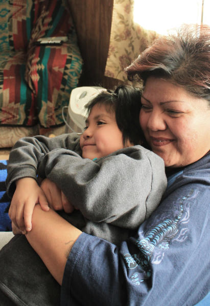 In this Jan. 2, 2013 photo, Robin Sanchez hugs her 5-year-old daughter, Nicholle, as she talks about surviving domestic violence during an interview at her home in Acoma Pueblo, N.M. Hope was high in 2010 when President Barack Obama signed the Tribal Law and Order Act, an overhaul intended to give tribal leaders more authority to combat crime on their reservations, but implementation of the law remains inconsistent on reservations nationwide. (AP Photo/Susan Montoya Bryan)