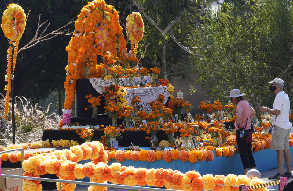 "People look at a community altar decorated with marigolds, sometimes called ""flowers of the dead,"" at Grand Park in Los Angeles, Thursday, Oct. 29, 2020. Mother and daughter Chicana artists Ofelia and Rosanna Esparza have overseen the design of the altar at Grand Park since 2013. It's one of 11 huge altars done in a collaboration between Grand Park and Self Help Graphics, an organization highlighting Chicano and Latino artists and social justice. (AP Photo/Damian Dovarganes)"