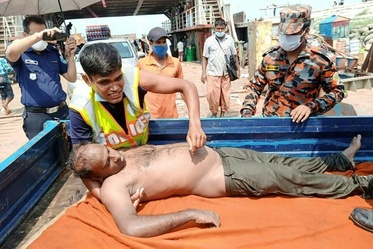 Police rescue an injured passenger from the overcrowded ferry in Madaripur, Bangladesh