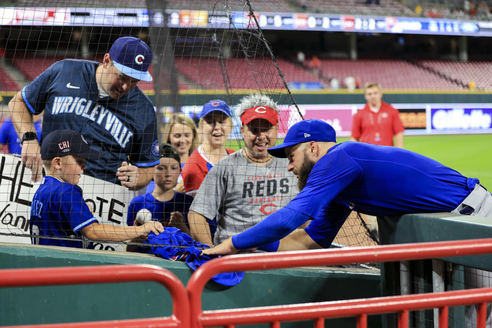 Chicago Cubs' David Bote, right, gives his jersey to fan Cam Kane, left, after the final out of a baseball game against the Cincinnati Reds in Cincinnati, Tuesday, Aug. 17, 2021. The Cubs won 2-1. (AP Photo/Aaron Doster)